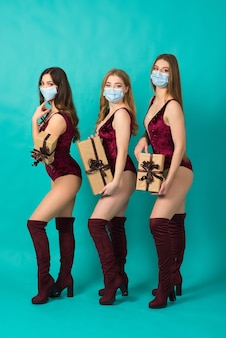 Three gorgeous women dressed in snow maiden costumes are smiling and screaming in protective mask on blue wall