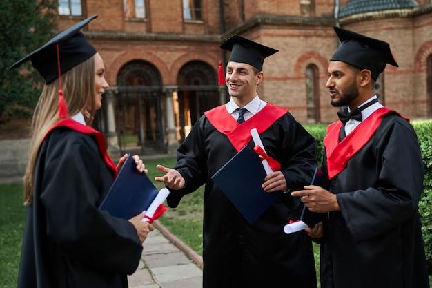 졸업 가운을 입은 세 명의 졸업생 친구가 손에 졸업장을 들고 캠퍼스에서 말하고 있습니다.