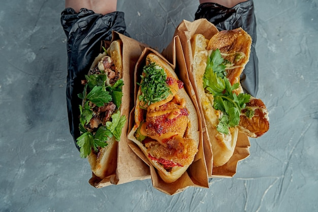 3つのギリシャのピタサンドイッチは手袋をはめた手で保持されます