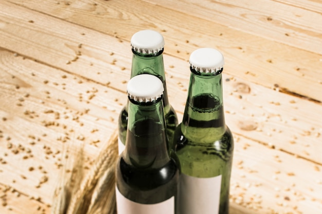 Three green alcoholic bottles and ears of wheat on wooden plank