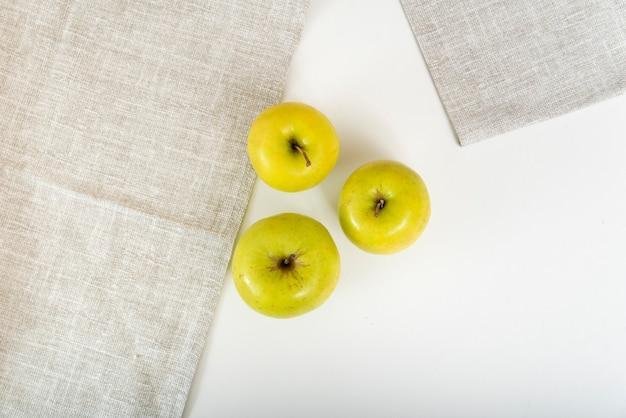 На столе рядом с текстильными салфетками три зеленых яблока. вид сверху.