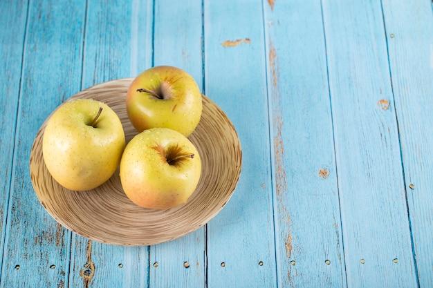 Три зеленые яблоки в тарелке