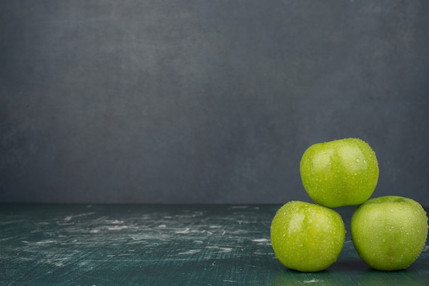 Three green apples on marble surface.