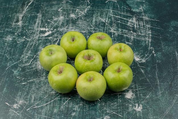 Tre mele verdi sulla superficie di marmo.