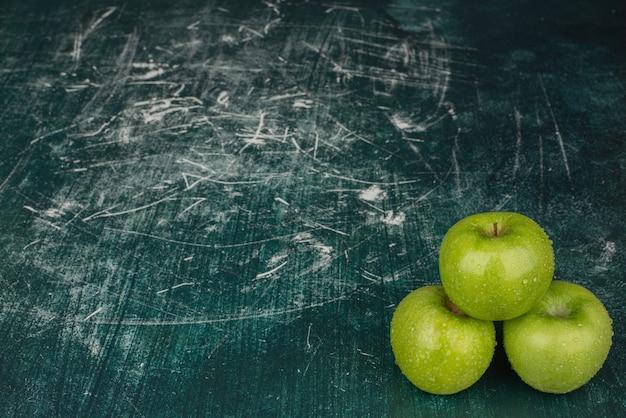 大理石の表面に3つの青リンゴ。