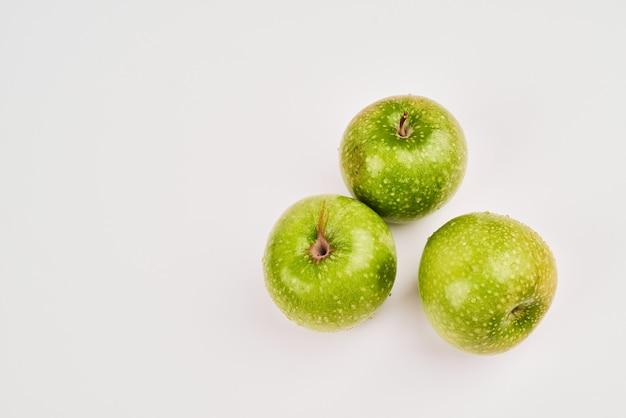 Три зеленых яблока на белой поверхности.
