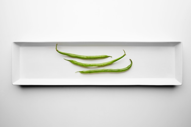 Tre fagiolini isolati al centro del piatto in ceramica bianca rettangolare sul tavolo