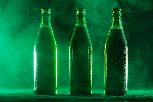 Three green beer bottles on a dusty background.