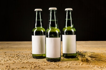 Three green beer bottles with ears of wheat on wooden surface