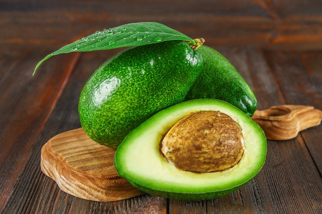 Three green raw ripe avocado fruits and a cut half with a bone with leaves