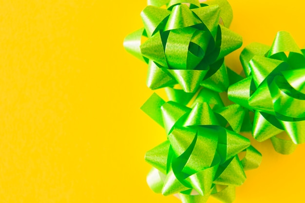 Three green satin ribbon bows on yellow background