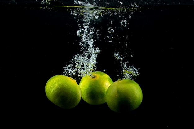 Three green tangerines in the water