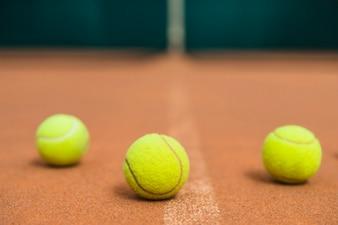 Three green tennis balls on the tennis court