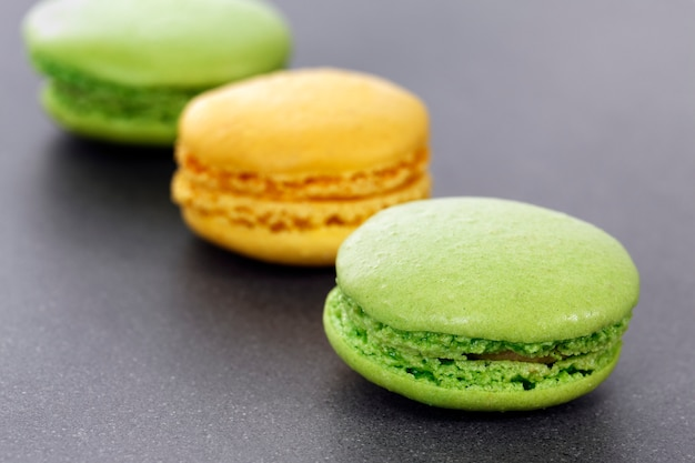 Three green and yellow macaroons in kitchen