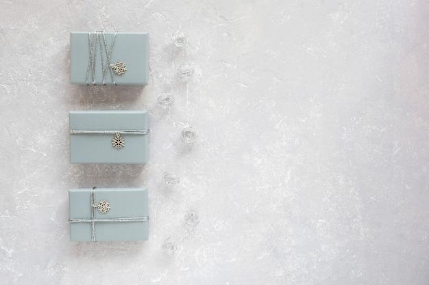 Три серые подарочные коробки, украшенные серебряной лентой и кулоном снежинка, на сером фоне, вид сверху, копировальное пространство
