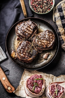 フライパンにベーコンをコーティングした牛ヒレ肉のグリルステーキ3枚。