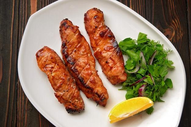 Три жареных на гриле филе лосося, форель, с зеленью и лимоном, на белой тарелке, на деревянном столе