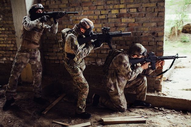 Three guys in ammunition are standing and hiding behind wall. first man is siting on his knees and targeting. other guys are standing behind each other. they have rifles in therir hands.