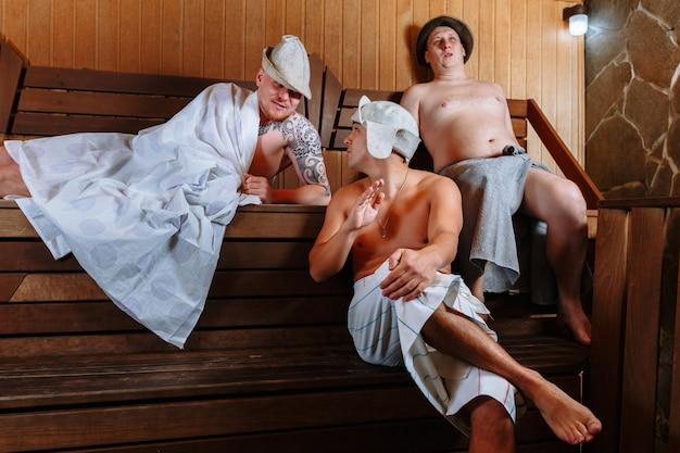 세 남자가 사우나에서 휴식을 취하고 활발한 대화를 나눕니다.