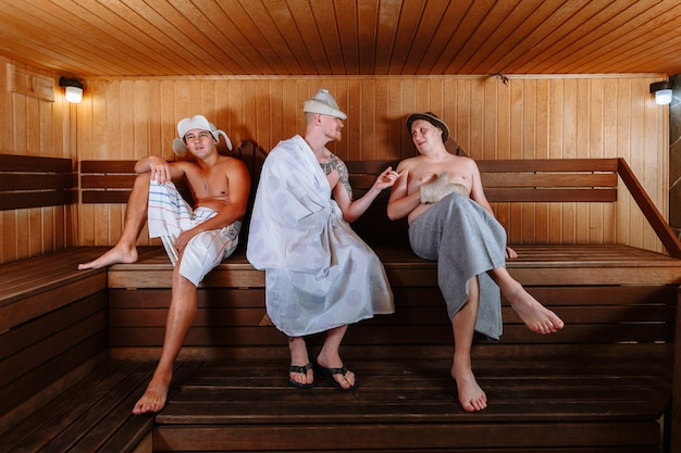 Three guys relax in the sauna and have a lively conversation Premium Photo