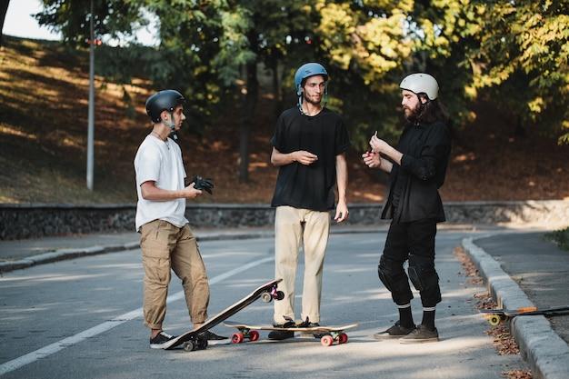 3人の男がスケートボードについて話します。高品質の写真