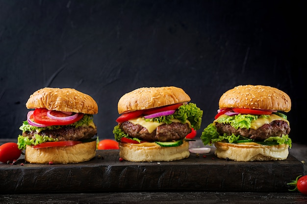 Three hamburger with beef meat burger and fresh vegetables on dark background.