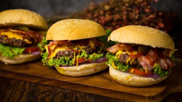 Три гамбургера с котлетой из говяжьего бургера, жареным луком, шпинатом, соусом кетчуп и сыром, подаются на деревянной разделочной доске на темном деревянном фоне.