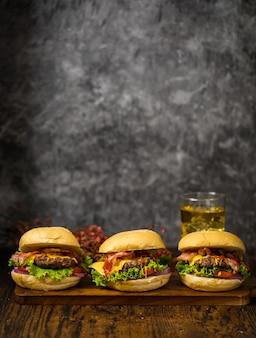 ダークウッドのボードとビールロフトの背景に、ビーフバーガー、ケチャップ、チーズを添えた3つのハンバーガーをお召し上がりいただけます。