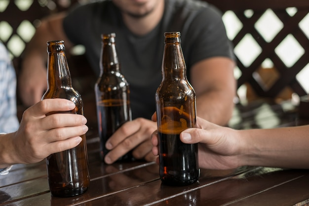 Three hands with beer bottles on table