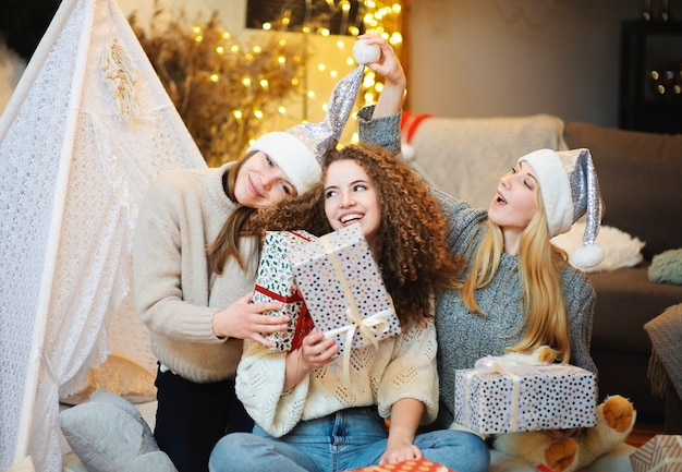 Three happy attractive young women sisters sitting on the floor at home gift wrapping giving christmas present