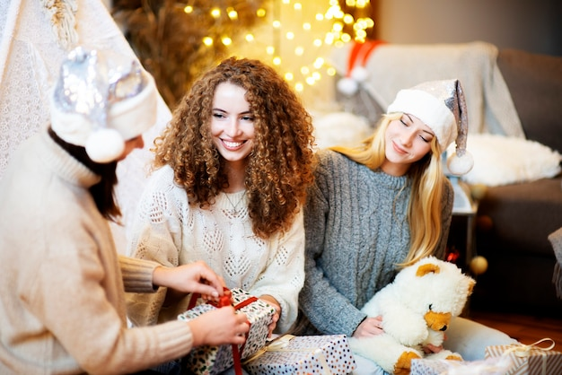 Three happy attractive young women sitting on the floor at home gift wrapping presents for christmas