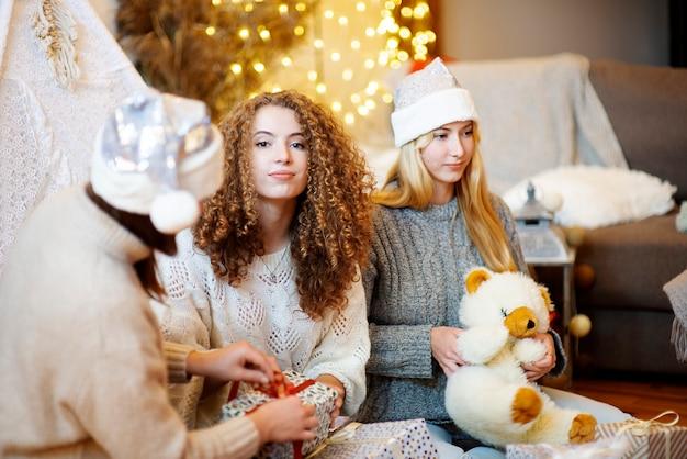 크리스마스 선물 포장 집에서 바닥에 앉아 세 행복 매력적인 젊은 여성