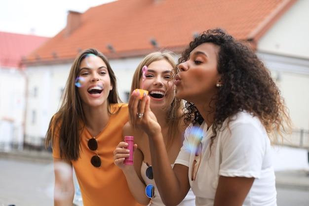 세 명의 행복한 아름다운 여성이 도시 거리에서 비누방울을 불고 있습니다.