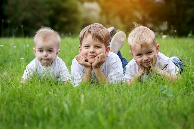 Three happy children (brothers)  resting on the green grass in summer