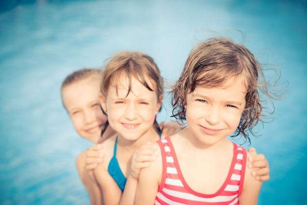 スイミングプールで3人の幸せな子供たち