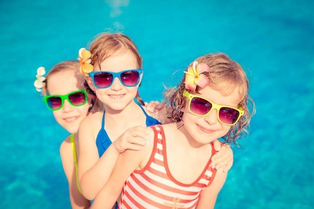 スイミングプールでカラフルなサングラスをかけた3人の幸せな子供たち