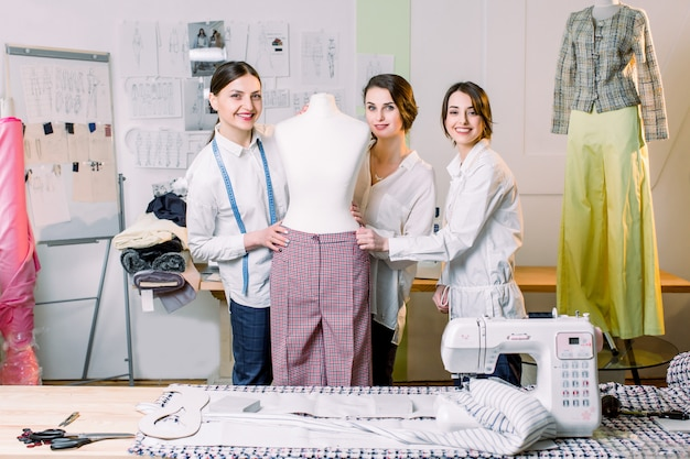 Three happy fashion designers working with fabric, clothing sketches, measuring materials on mannequin at the studio full of tailoring tools and equipment