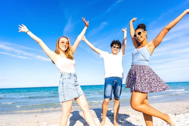 腕を上げて見て笑ってポーズをとってビーチで楽しんでいる3人の幸せな友人