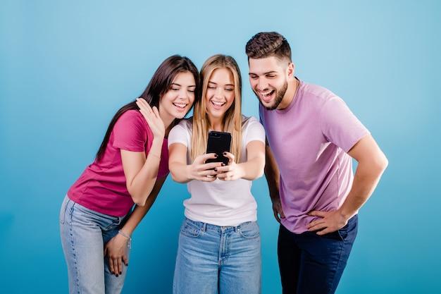 Три счастливые друзья, глядя на экран телефона и улыбаясь на синем