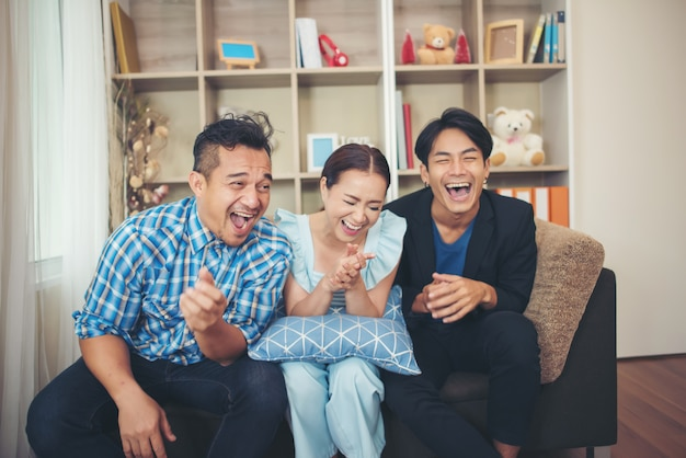 Three happy friends talking and big laughing after watching joke story
