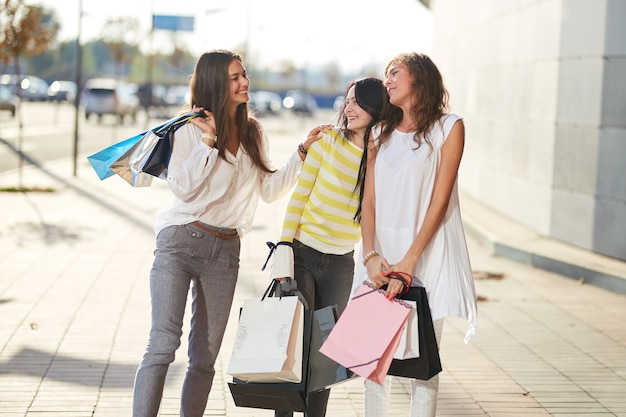 スタイリッシュなカジュアルな服を着た3人の幸せな女の子が買い物袋を持って歩く