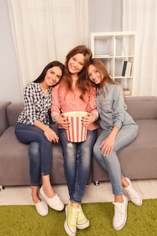Three happy girls having party and watching film with popcorn