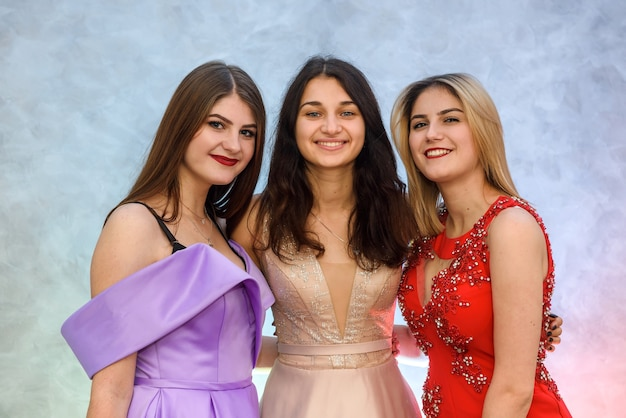 추상적인 배경에 포즈 우아한 드레스에 세 행복 한 여자. 축하 개념
