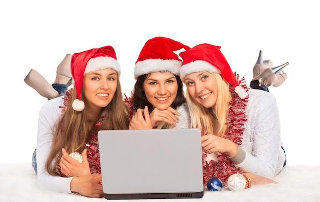 Три счастливые девушки с ноутбуком и украшениями