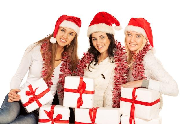 Три счастливые девушки с рождественскими подарками и украшениями