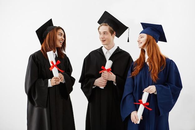 Tre laureati felici che sorridono parlando dei diplomi di tenuta.