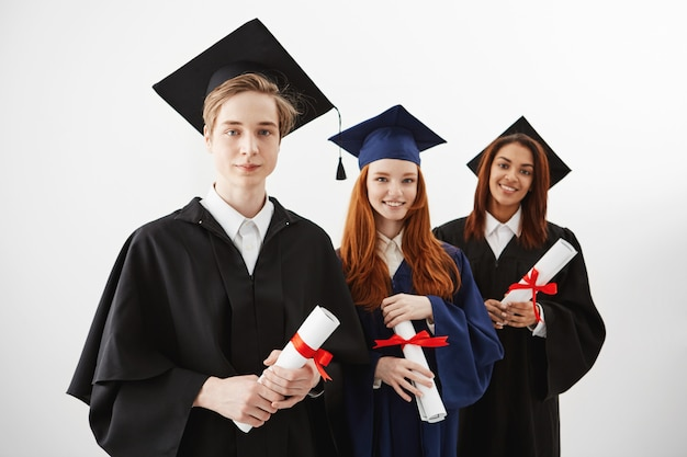 Трое счастливых выпускников международных университетов, улыбаясь, радуясь, имеющих дипломы. будущие юристы или инженеры.