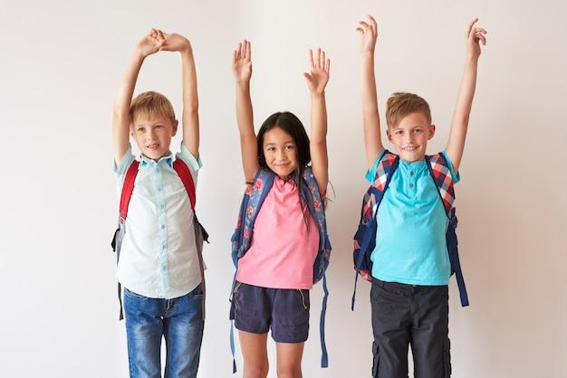 Three happy kids raising hands