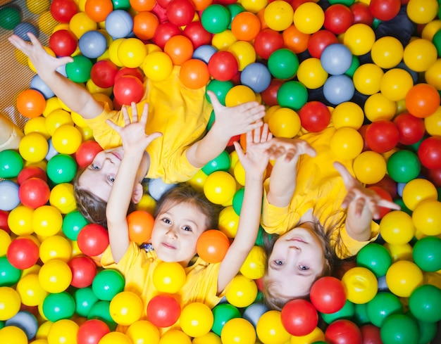 Three happy little kids in ball pool smiling