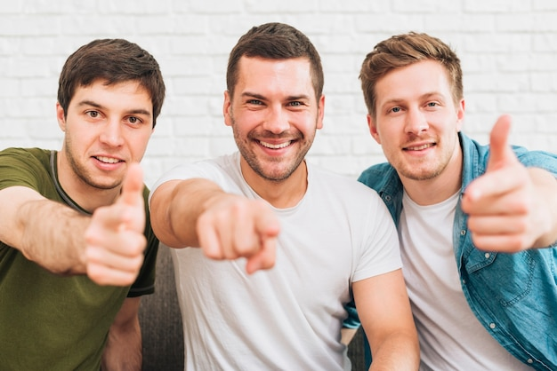 Three happy male friends pointing finger toward camera